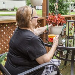 A woman sits on her patio and tends to plants