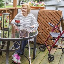A woman sits on a patio next to a walker