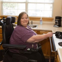 A woman in a wheelchair stirs a pot on the stove