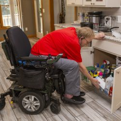 A man in a wheelchair bends down to open a kitchen door with slide-out shelf